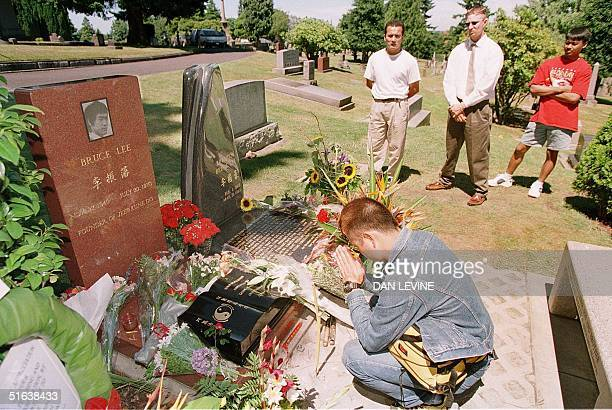 Yuki Shigeoka of Tokyo sits by the gravesite of martial arts leader and movie star Bruce Lee at a cemetary in Seattle WA on the day of the 25th...
