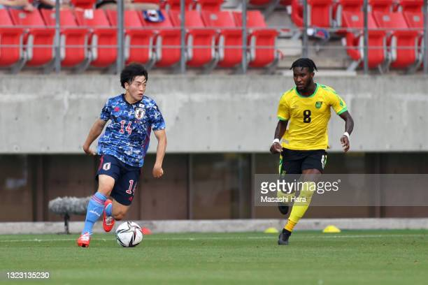 Yuki Soma of Japan U-24 takes on Oniel Fisher of Jamaica during the international friendly match between Japan U-24 and Jamaica at the Toyota Stadium...