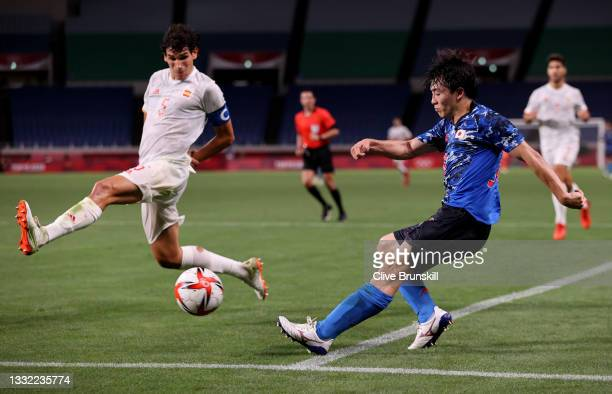 Yuki Soma of Team Japan attempts to cross the ball past Jesus Vallejo of Team Spain during the Men's Football Semi-final match between Japan and...
