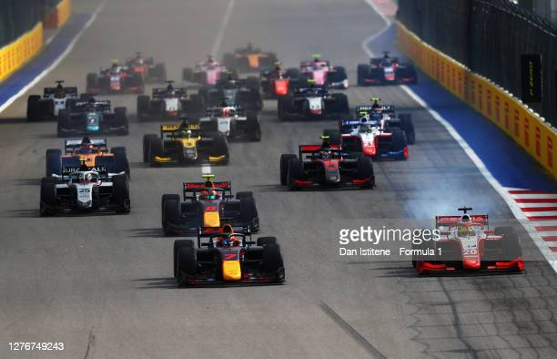 Yuki Tsunoda of Japan and Carlin and Mick Schumacher of Germany and Prema Racing battle for position ahead of the field at the start during the...