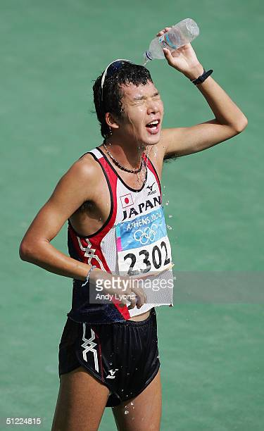 Yuki Yamazaki of Japan cools off with water after finishing the men's 50 kilometer race walk after getting red carded and disqualified on August 27...