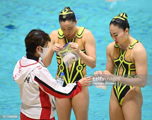 Yukiko Inui and Megumu Yoshida receive face masks from Japan national team head coach Masayo Imura after competing in the Duet Free Routine on day...