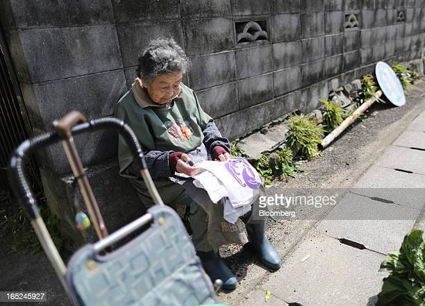 Yukiko Watanabe sits by the side of a road next to her walking stick and stroller on Gogo Island in Matsuyama Ehime Prefecture Japan on Friday March...