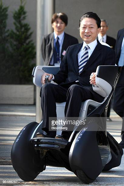 Yukio Hatoyama Japan's prime minister center rides on a Toyota Motor Corp i REAL electric personal mobility following a news conference announcing...