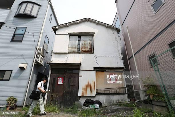 Yukio Iwasaki an official at Kita ward's urban development construction division inspects an abandoned house in Kita ward in Tokyo Japan on Tuesday...