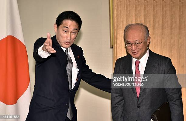 Yukiya Amano , director general of the International Atomic Energy Agency is greeted by Japanese Foreign Minister Fumio Kishida for their talks at...