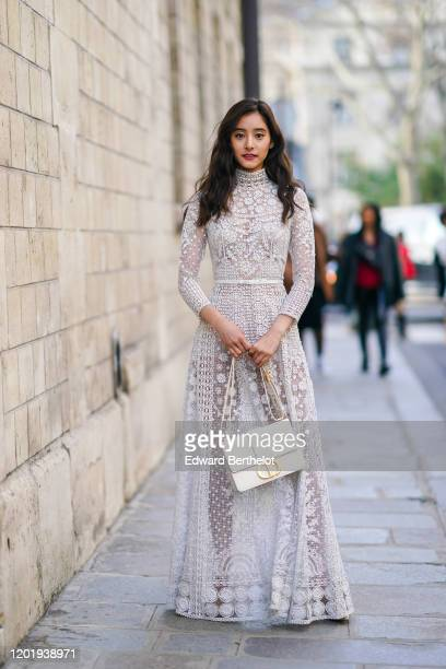 "Yuko Araki wears a white lace mesh dress with floral embroidery, a ""CD"" Dior bag, outside Dior, during Paris Fashion Week - Haute Couture..."