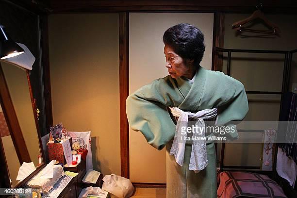 Yuko Asakusa adjusts her kimono at her home studio in the Asakusa District on November 6 2014 in Tokyo Japan 91 year old Yuko Asakusa became a Geisha...