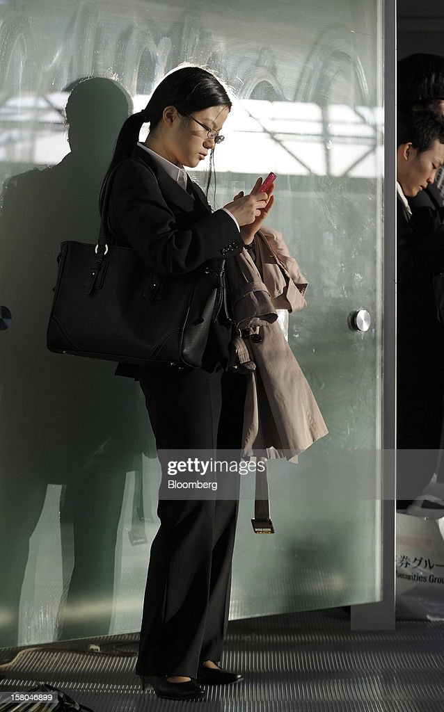 Yuko Nishiyama, a university student, uses her smartphone at a job fair hosted by Mynavi Corp. in Tokyo, Japan, on Saturday, Dec. 8, 2012. In Japan, many students accept job offers from large companies six months before graduating and may stay with the same employer until retirement, said Yoshihide Suzuki, an administrative director at the career center at Waseda University. Photographer: Akio Kon/Bloomberg via Getty Images