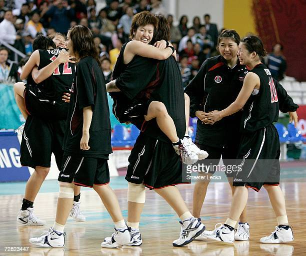 Yuko Oga of Japan and teammates celebrate winning 74 70 over the Republic of Korea in the Women's Basketball Bronze Medal Match during the 15th Asian...