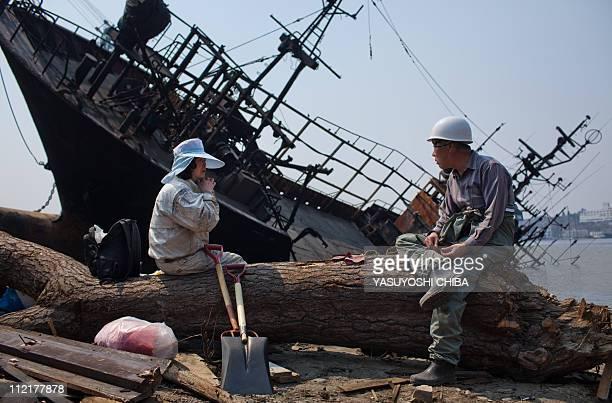 Yuko Takahashi sits on a wood at her property as she talks with Tomio Takahashi who lost his shipyard next to her home in Kesennuma city Miyagi...