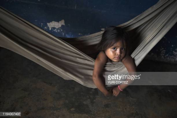 Yukpa indigenous girl rests in a hammock near her grandmother who lies with fever due to malaria, at their house in Los Angeles del Tukuko community,...