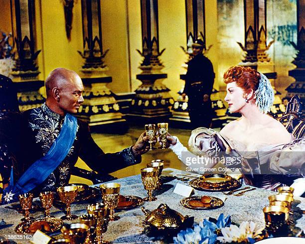 Yul Brynner Russianborn US actor and Deborah Kerr both in costume seated at a dining table in a publicity still issued for the film 'The King and I'...