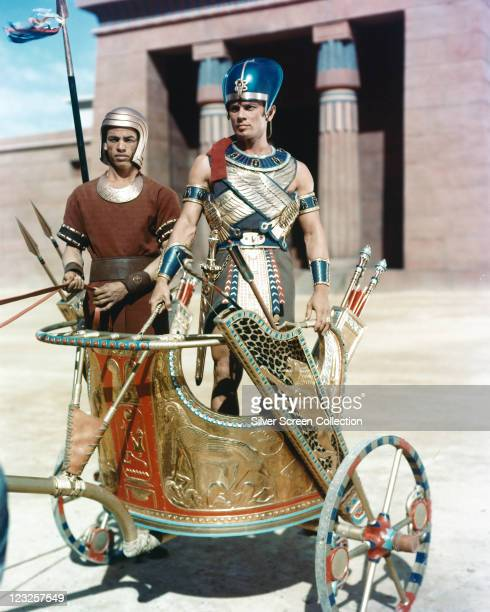 Yul Brynner Russianborn US actor dressed in gold armor standing on a chariot in a publicity portrait issued for the film 'The Ten Commandments' 1956...