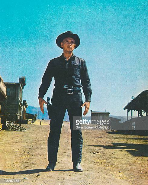 Yul Brynner Russianborn US actor wearing a black cowboy hat as he prepares to reach for his gun in a holster in a publicity still issued for the film...