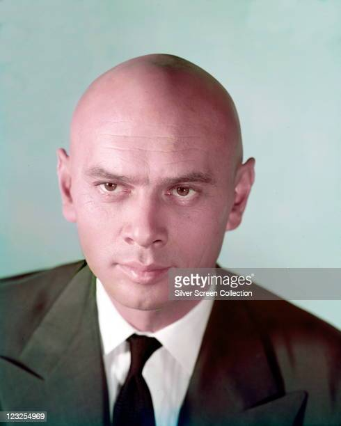 Yul Brynner Russianborn US actor wearing a green jacket with a white shirt and a black tie in a studio portrait against a light blue background circa...