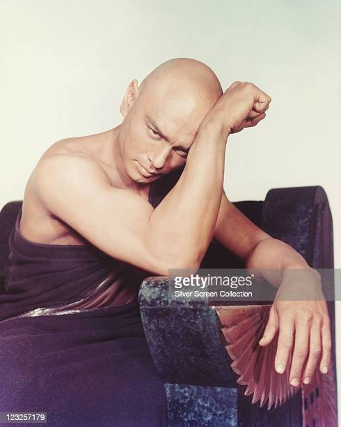 Yul Brynner Russianborn US actor wearing a robe with his head resting against his arm which rests on the arm of a chair in a publicity portrait...