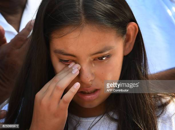Yuleni Avelica daughter of Romulo Avelica who was arrested by immigration officials after dropping off a daughter at school react during a press...