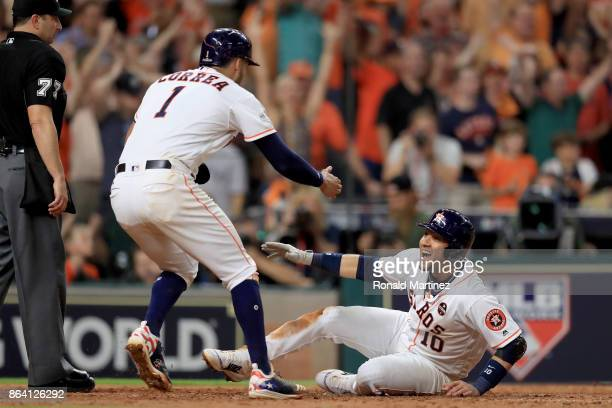 Yuli Gurriel and Carlos Correa of the Houston Astros celebrate after they scored off of a double hit by Alex Bregman against David Robertson of the...