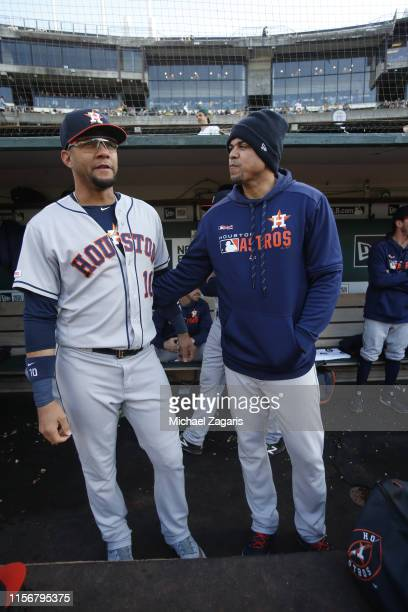 Yuli Gurriel and Hitting Coach Alex Cintron of the Houston Astros talk in the dugout prior to the game against the Oakland Athletics at the...