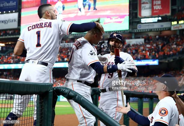Yuli Gurriel of the Houston Astros celebrates a solo home run with Carlos Correa and Marwin Gonzalez during the second inning against the Los Angeles...