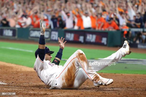 Yuli Gurriel of the Houston Astros celebrates as he slides home to score off of a double hit by Alex Bregman against David Robertson of the New York...