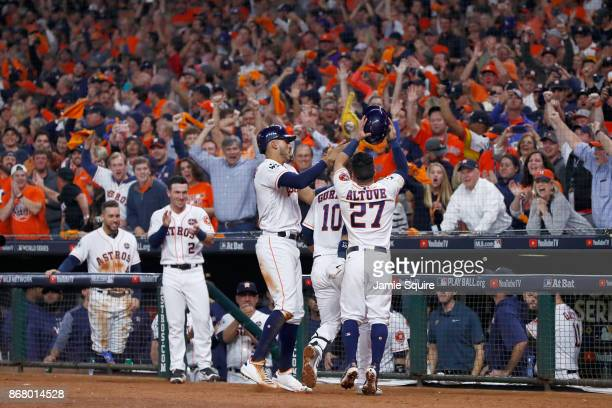 Yuli Gurriel of the Houston Astros celebrates with Carlos Correa and Jose Altuve after hitting a three run home run during the fourth inning against...
