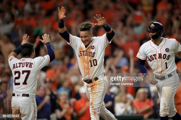 Yuli Gurriel of the Houston Astros celebrates with teammates Jose Altuve and Carlos Correa after scoring off of a double hit by Brian McCann against...