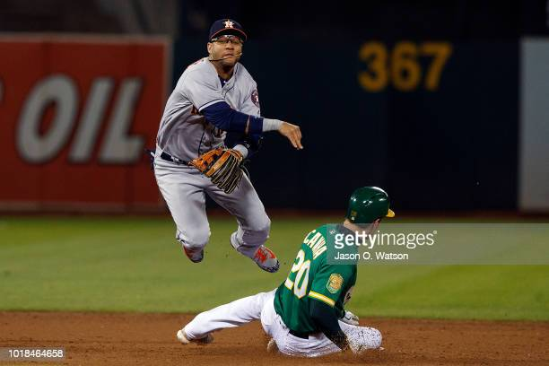 Yuli Gurriel of the Houston Astros completes a double play over Mark Canha of the Oakland Athletics during the fifth inning at the Oakland Coliseum...
