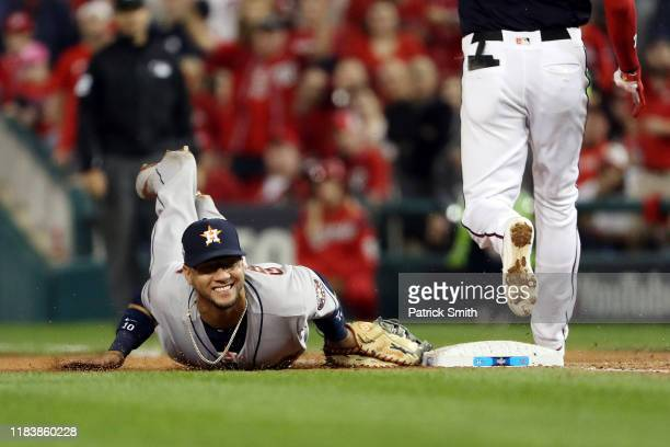 Yuli Gurriel of the Houston Astros dives into first base to retire Trea Turner of the Washington Nationals on a groundout during the sixth inning in...