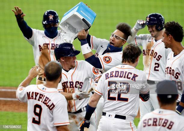 Yuli Gurriel of the Houston Astros dumps ice over the head of Myles Straw after Straw singled in the winning run in the 11th inning against the...