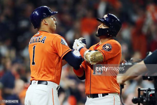 Yuli Gurriel of the Houston Astros is congratulated by his teammate Carlos Correa after hitting a solo home run against the Washington Nationals...