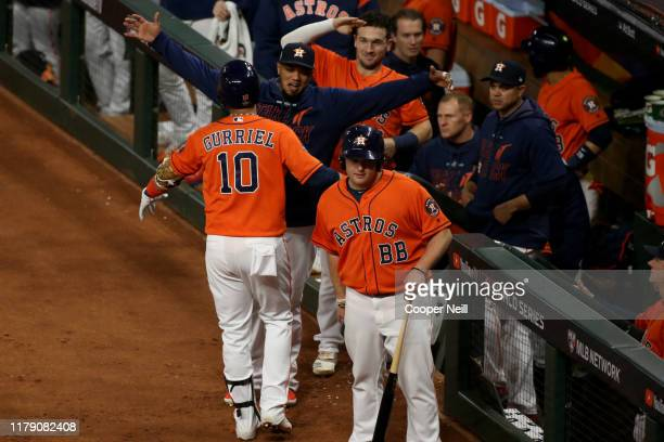 Yuli Gurriel of the Houston Astros is greeted in the dugout after hitting a solo home run in the second inning during Game 7 of the 2019 World Series...