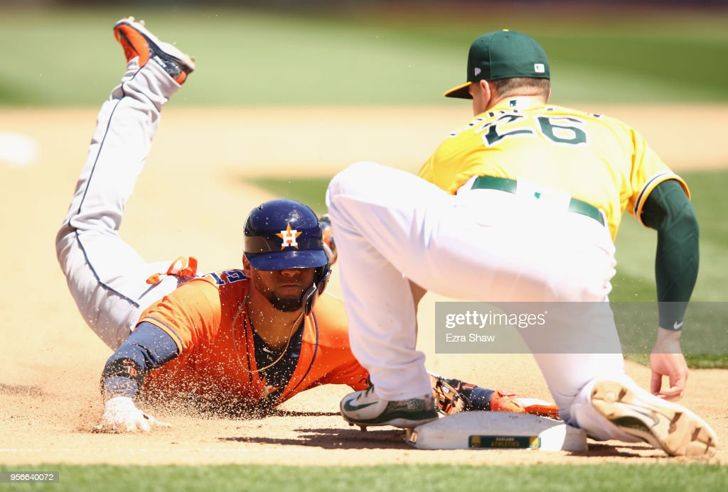 Yuli Gurriel #10 of the Houston Astros is tagged out by Matt Chapman #26 of the Oakland Athletics as he attempted to steal third base in the eighth inning at Oakland Alameda Coliseum on May 9, 2018 in Oakland, California.