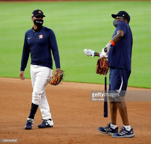 Yuli Gurriel of the Houston Astros, left, and manager Dusty Baker wear masks during the third day of Summer Camp workouts at Minute Maid Park on July...