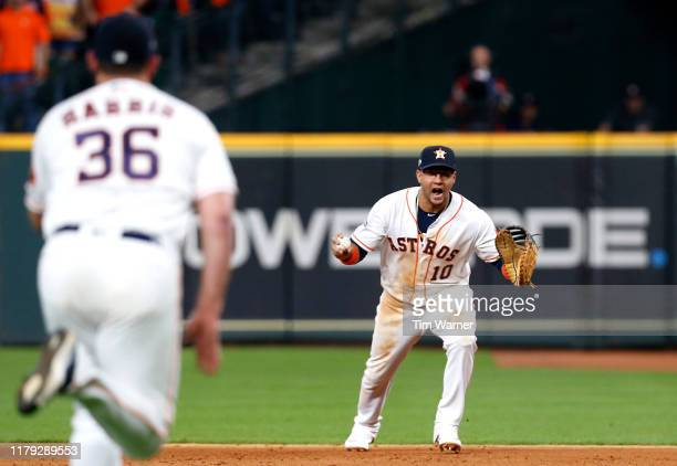 Yuli Gurriel of the Houston Astros reacts with the ball before tossing the ball to Will Harris to make the final out to win Game 2 of the ALDS by...