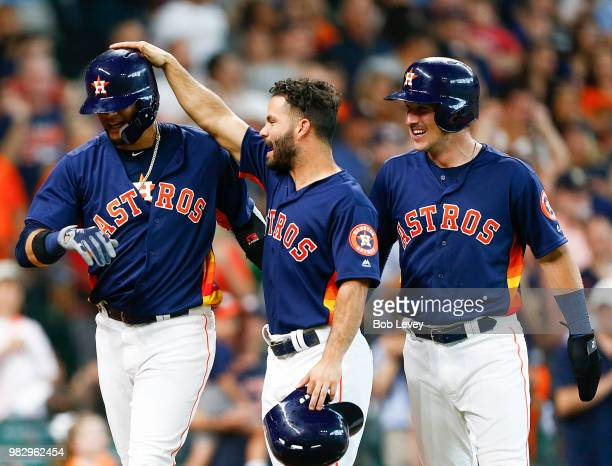 Yuli Gurriel of the Houston Astros receives congratulations from Jose Altuve and Alex Bregman after hitting a grand slam in the second inning against...