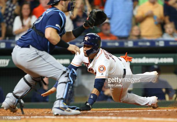 Yuli Gurriel of the Houston Astros scores in the seventh inning as Mike Zunino of the Tampa Bay Rays waits for the ball at Minute Maid Park on August...