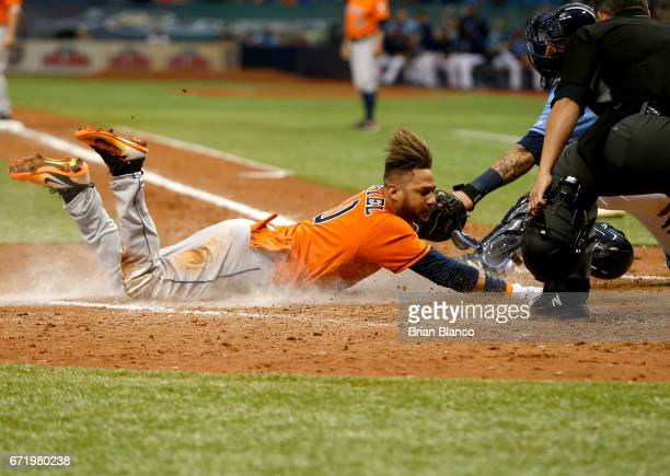 Yuli Gurriel of the Houston Astros slides home ahead of catcher Jesus Sucre of the Tampa Bay Rays to score off of the sacrifice fly by Evan Gattis...