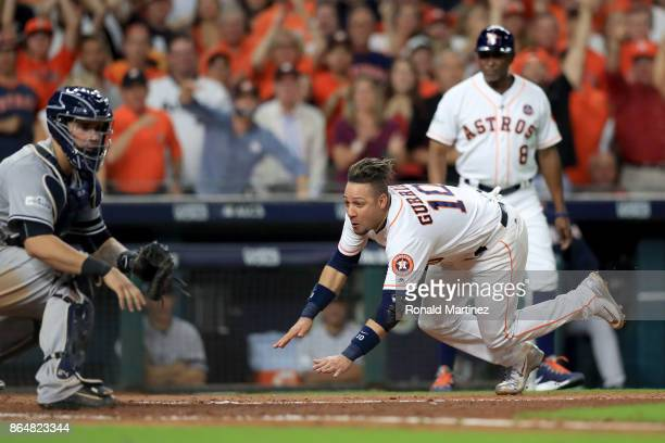 Yuli Gurriel of the Houston Astros slides safe at home plate against Gary Sanchez of the New York Yankees off of a double hit by Brian McCann against...