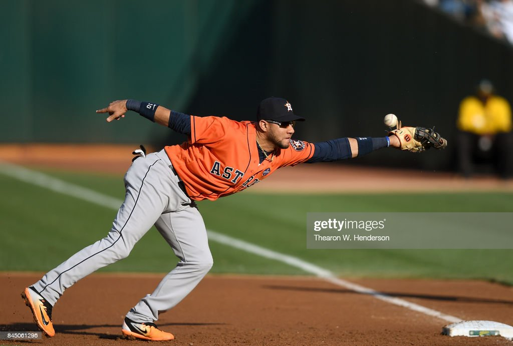 Yuli Gurriel #10 of the Houston Astros watches the ball hit off his glove for a single off the bat of Matt Olson #28 of the Oakland Athletics in the bottom of the first inning of the second game of a doubleheader at Oakland Alameda Coliseum on September 9, 2017 in Oakland, California.