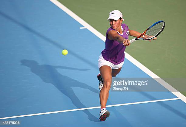Yulia Putintseva of Kazakhstan returns a shot during her match against Alize Conrnet of France during day one of the 2014 WTA Guangzhou Open at Taint...