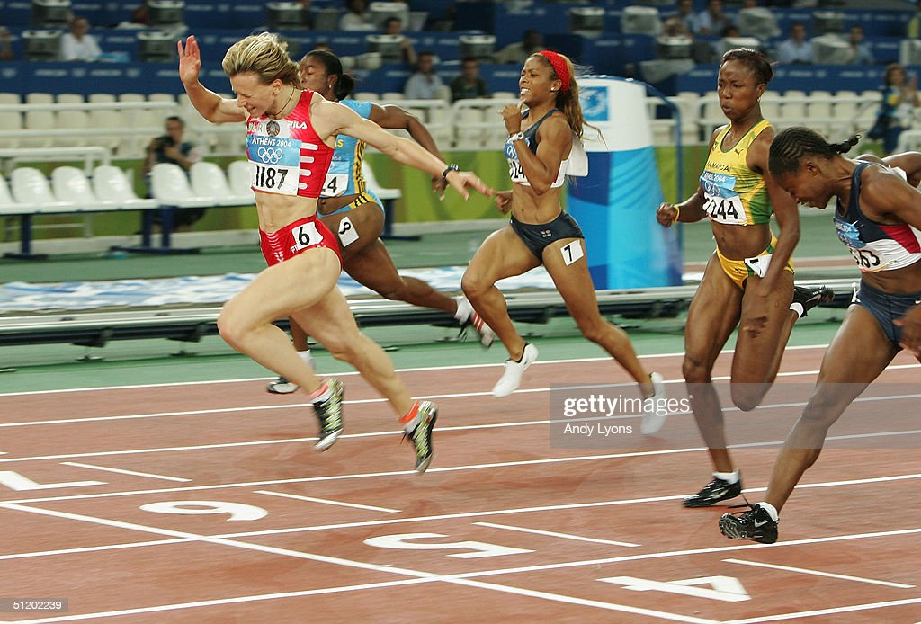 Yuliya Nesterenko of Belarus crosses the finish line as she wins gold in the women's 100 metre final on August 21, 2004 during the Athens 2004 Summer Olympic Games at the Olympic Stadium in the Sports Complex in Athens, Greece.