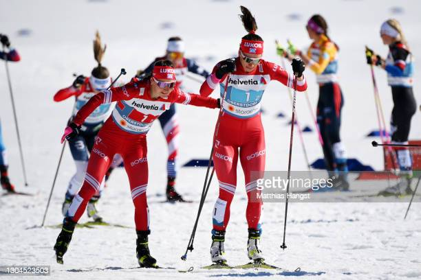 Yuliya Stupak of Russian Ski Federation taps on Natalia Nepryaeva of Russian Ski federation in an exchange during the Women's Cross Country Team...