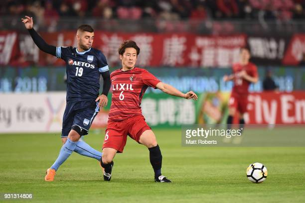 Yuma Suzuki competes for the ball against Chris Zulea of Sydney FC during the AFC Champions League Group H match between Kashima Antlers and Sydney...