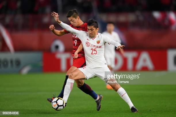 Yuma Suzuki of Kashima Antlers and Odil Ahmedov of Shanghai SIPG compete for the ball during the AFC Champions League Round of 16 first leg match...