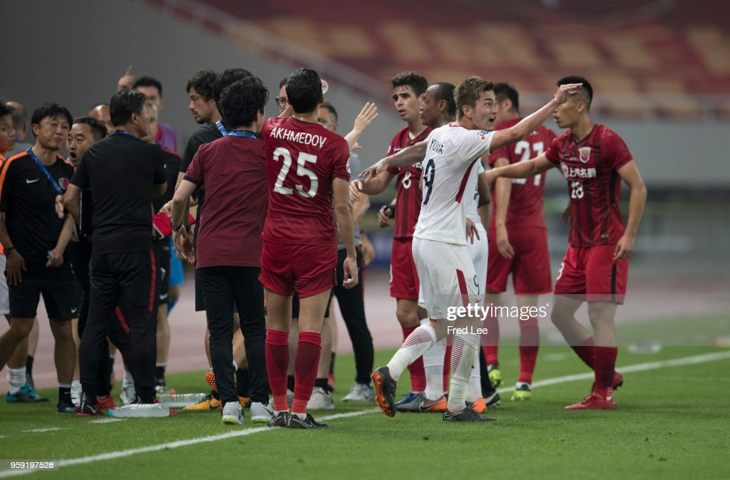 Yuma Suzuki #9 of Kashima Antlers and Shi Ke #5 of hanghai SIPG clash during the AFC Champions League Round of 16 match between Shanghai SIPG v Kashima Antlers at the Shanghai Stadium on May 16, 2018 in Shanghai, China.