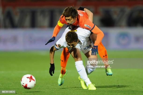 Yuma Suzuki of Kashima Antlers controls the ball under pressure of Kosuke Kikuchi of Omiya Ardija during the J.League J1 match between Omiya Ardija...