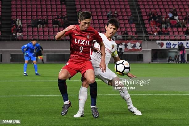 Yuma Suzuki of Kashima Antlers controls the ball under pressure of Wang Shenchao of Shanghai SIPG during the AFC Champions League Round of 16 first...