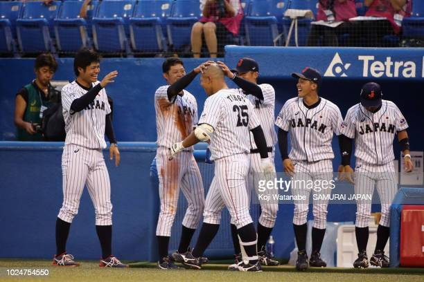 Yuma Tongu of Samurai Japan Collegiate is congratulated by his team mates after hitting a two-run homer in the first inning during the game between...